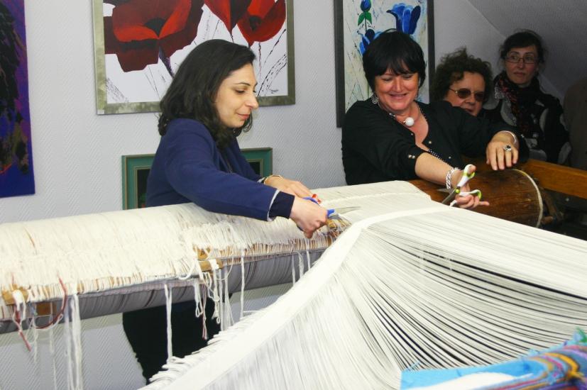 Bina Baitel et la lissière Françoise Vernaudon coupent les derniers fils de chaîne pour libérer le tapis Confluentia du métier à tisser (mai 2014)