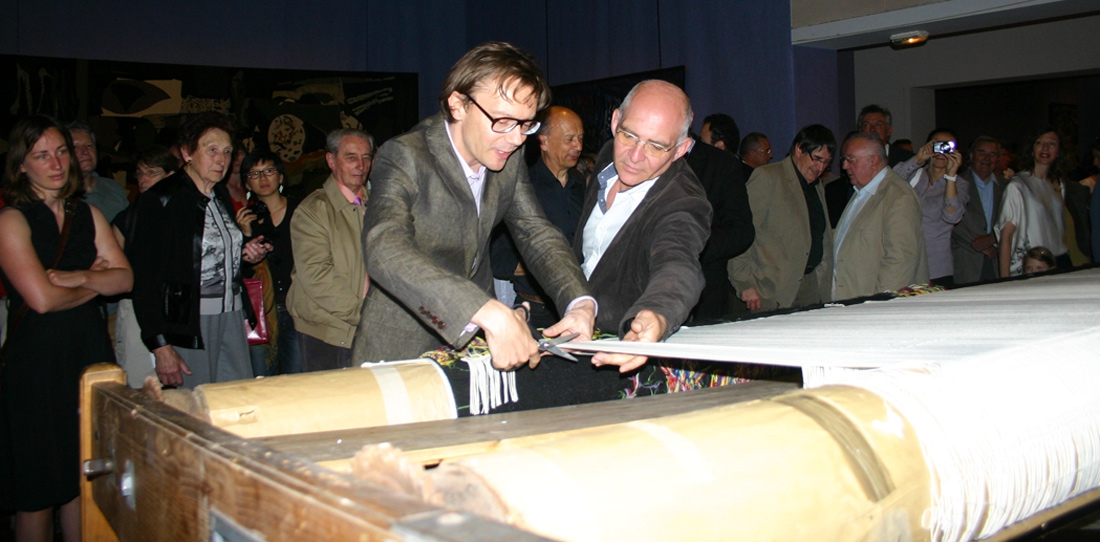 Mathieu Mercier cutting his tapestry off the loom, next to Pascal Legoueix